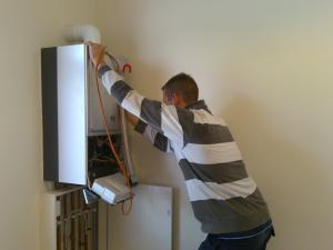 Plumbing contractor setting up a tankless heater during an installation